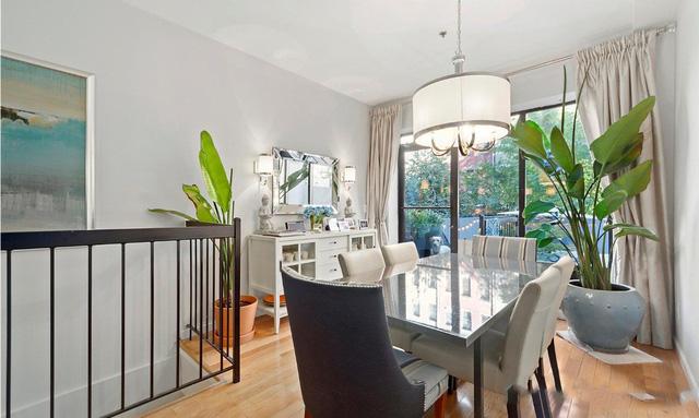 Phòng ăn ở tầng trên tận dụng được ánh sáng tự nhiên nhờ những ô cửa sổ sát sàn cỡ lớn. Ngoài ra, hai chậu cây xanh khổng lồ trong phòng cũng giúp mang thiên nhiên vào cho phòng ăn đơn giản này.
