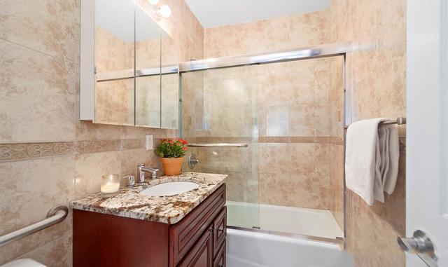 Trong phòng ngủ này cũng có một nhà tắm để tiện cho việc vệ sinh cá nhân của chủ nhà. Bồn tắm được ngăn cách với không gian bên ngoài bằng cửa kính dạng lửng giúp không khí trong nhà tắm được thoáng hơn rất nhiều. Tường được ốp bằng đá grantit sang trọng và sạch sẽ